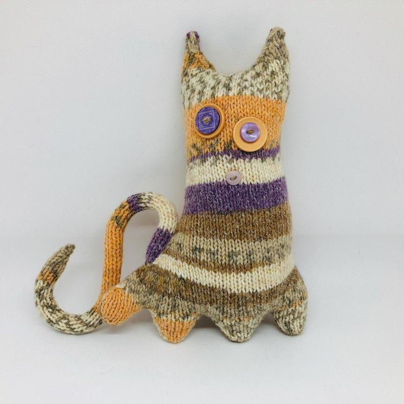 Curious Creature - Cynthia (a circumspect creature). Handknitted whimsy with polyester wadding, button features, wired tail.  Height: 9 ins; width: 9 ins; depth: 3 ins.  £25