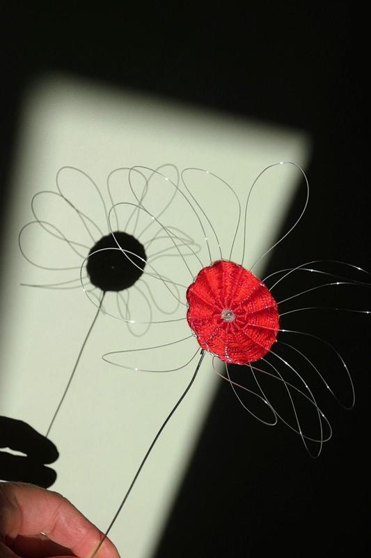 Flower woven in fishing line and red cotton on a wire stem