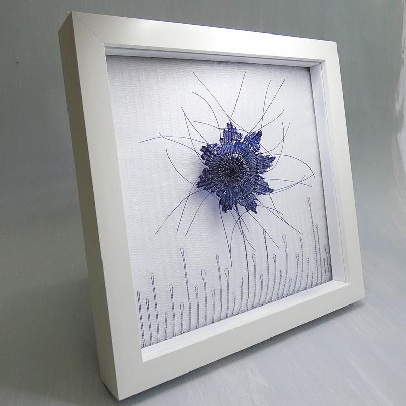 A woven flower in hand dyed blue fishing line interwoven in a clear fishing line woven background and framed in a white box frame