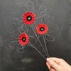 three woven poppies by Lucy Sugden held against a slate grey background