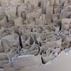 Fine paper and clay slip folds in ceramic vessel