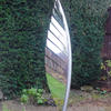 Spring Leaf 2020 by Diane Maclean  A sculpture for a garden.  Stainless steel.  The leaf picks up light and reflections from its surrounds.
