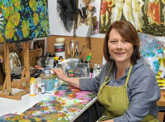 Photo of artist Sara Button at work in her studio.