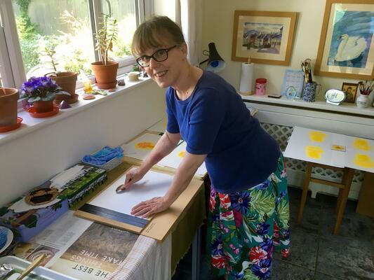 Teresa Newham hand printing a reduction linocut print
