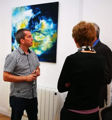 Alexander discussing his work during an exhibition.