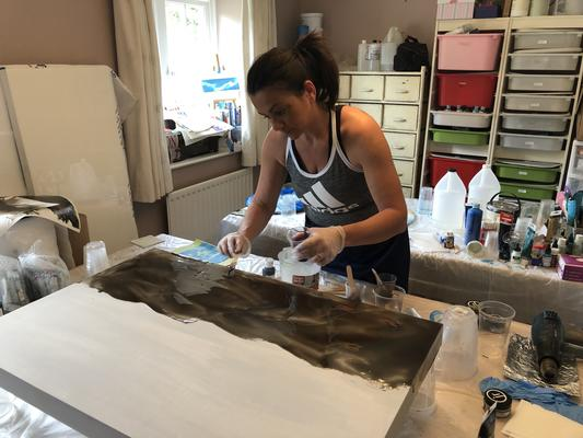 Applying the first layer of tinted resin onto a wood panel