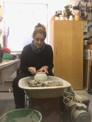At the potter's wheel in the garage/studio.